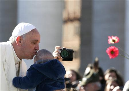 Pope Francis kisses a child as he arrives to lead the general audience in Saint Peter's Square at the Vatican March 5, 2014. REUTERS/Alessandro Bianchi