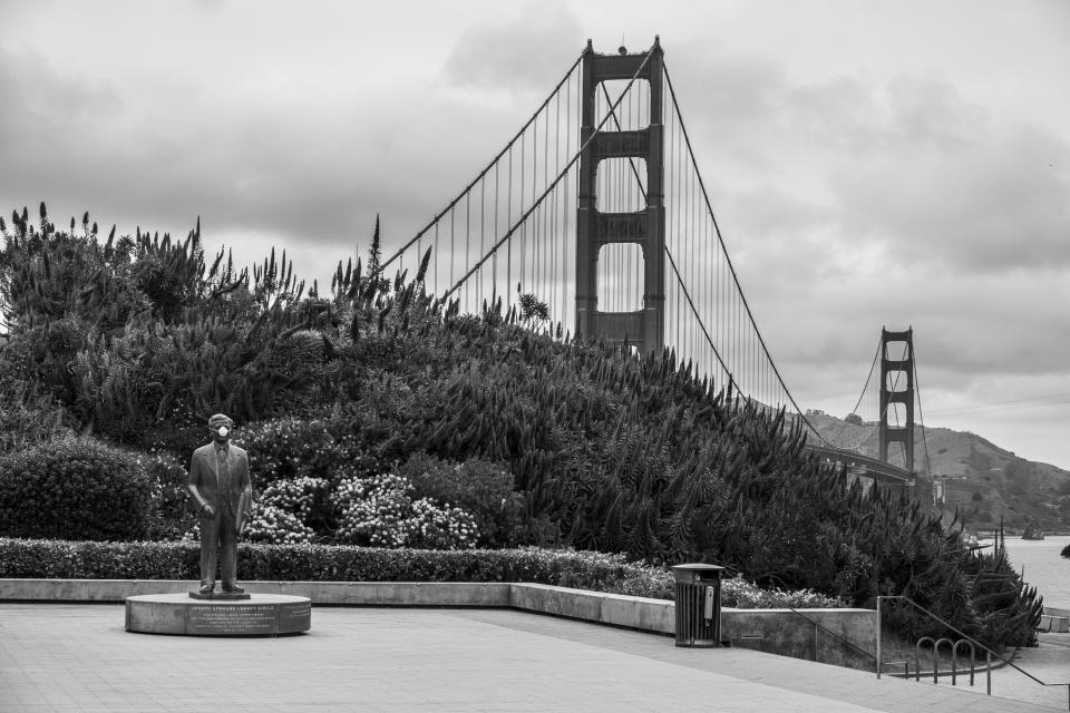A mask covers the mouth on the statue of Golden Gate Bridge chief engineer Joseph Strauss at an empty visitors plaza in San Francisco on April 17, 2020. Normally, the months leading into summer bring bustling crowds to the city's famous landmarks, but this year, because of the coronavirus threat they sit empty and quiet. Some parts are like eerie ghost towns or stark scenes from a science fiction movie. (AP Photo/Eric Risberg)