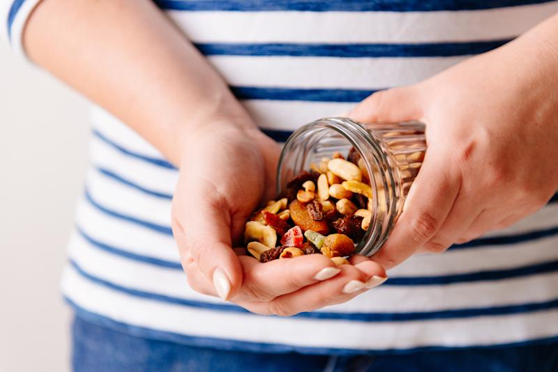 A pair of hands holding an open jar of dried fruits and nuts