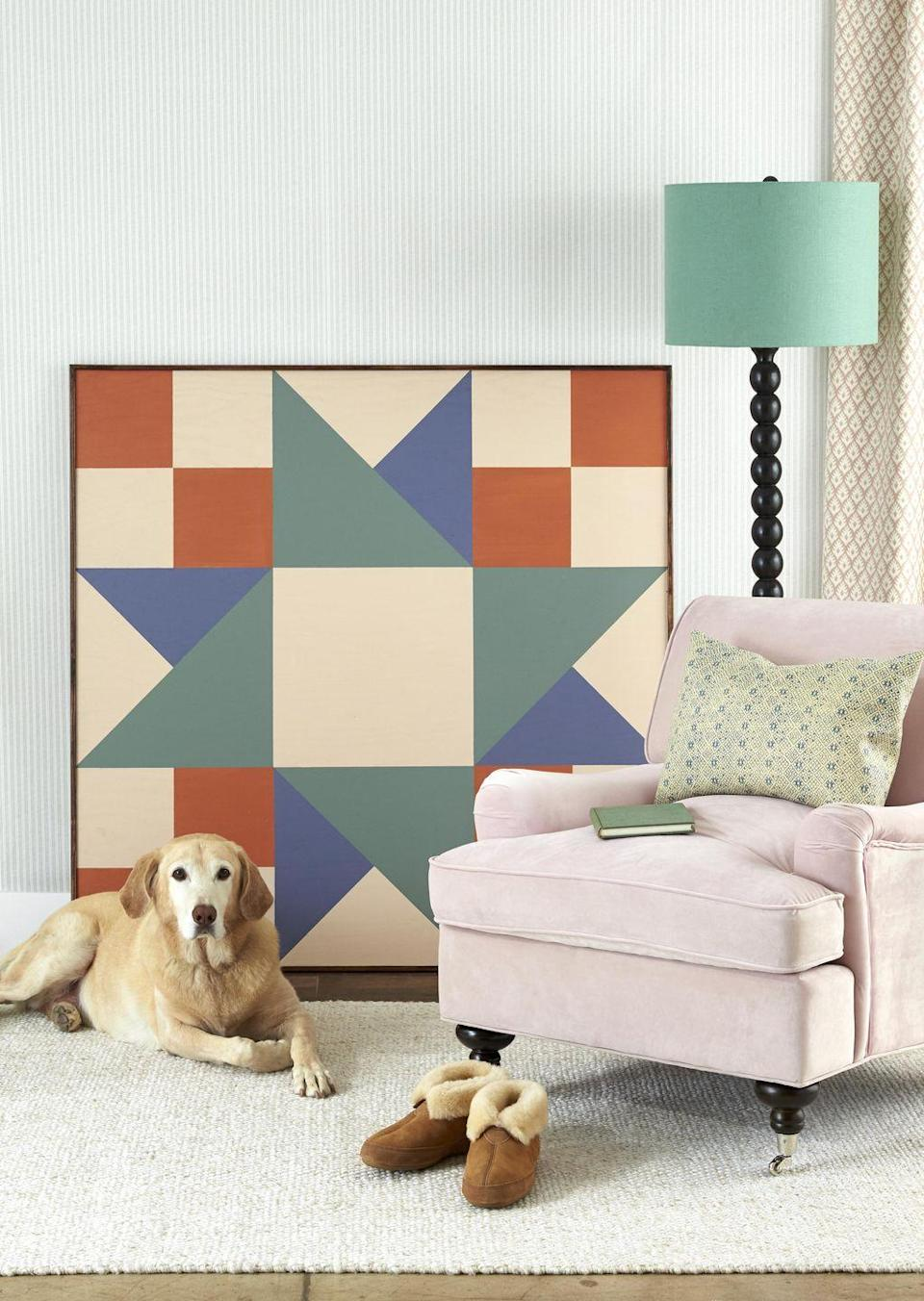 <p>Gus loves the hanging out with the colorful painted quilt square. Simply lean it against the wall for easy installation.</p><p><strong>To make:</strong> A large-scale piece of painted plywood lends graphic punch to any space. First, cut a piece of plywood to desired size<br>(ours is four feet square). Draw a quilt block (here, Twin Star–style) on the wood with pencil, using a ruler or painter's tape for straight lines, then paint with acrylic paint. Nail strips of 1/2-inch trim along<br>the edges to finish. Lean or hang on the wall.<br></p>