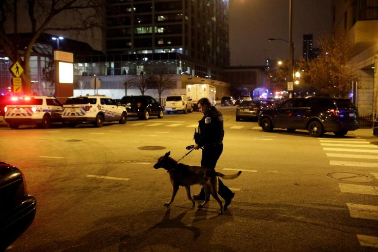 A Chicago police officer walks with his dog outside Mercy Hospital where an argument in the parking lot escalated into a shooting that left three dead