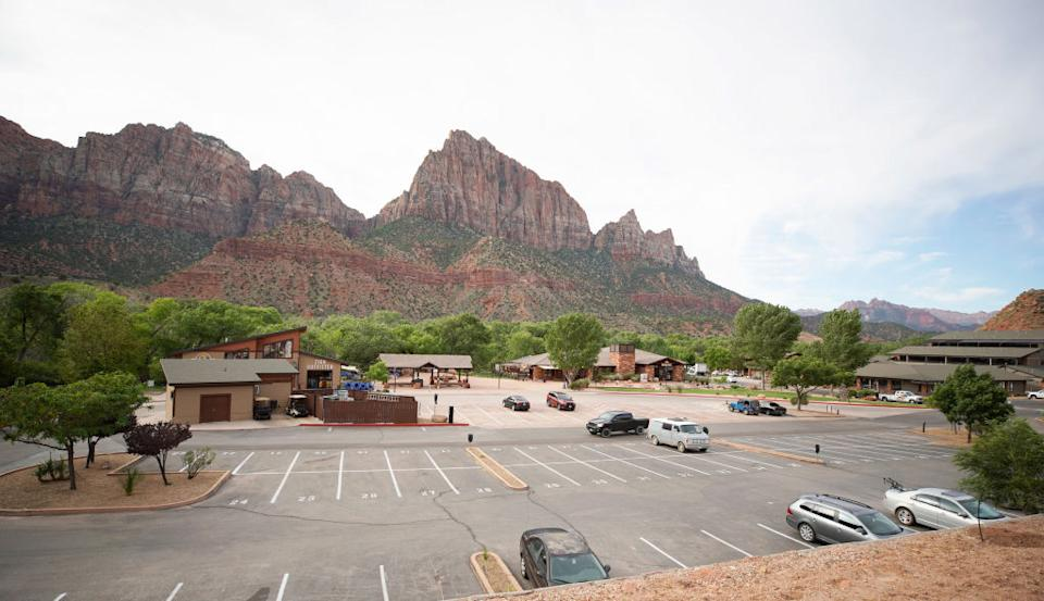 A few cars are parked in the normally filled parking lot outside the walk up entrance to Zion National Park.