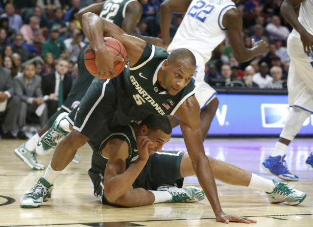 Michigan State center Adreian Payne (5) falls over teammate Denzel Valentine after securing a rebound during the first half of an NCAA college basketball game against Kentucky on Tuesday, Nov. 12, 2013, in Chicago. (AP Photo/Charles Rex Arbogast)
