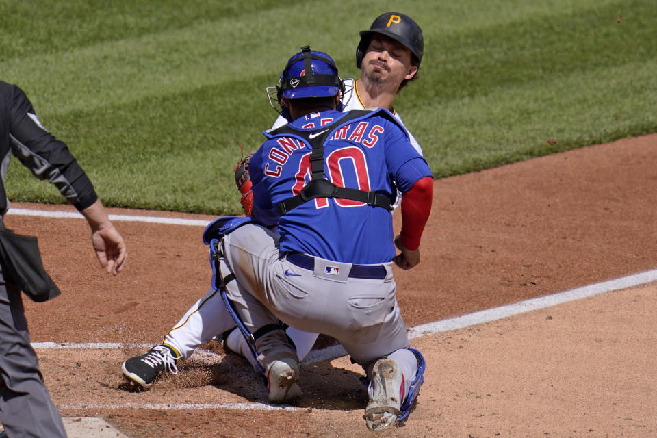 Pittsburgh Pirates' Bryan Reynolds, right, is tagged out by Chicago Cubs catcher Willson Contreras attempting to score on a fielder's choice during the fifth inning of a baseball game in Pittsburgh, Sunday, April 11, 2021. (AP Photo/Gene J. Puskar)