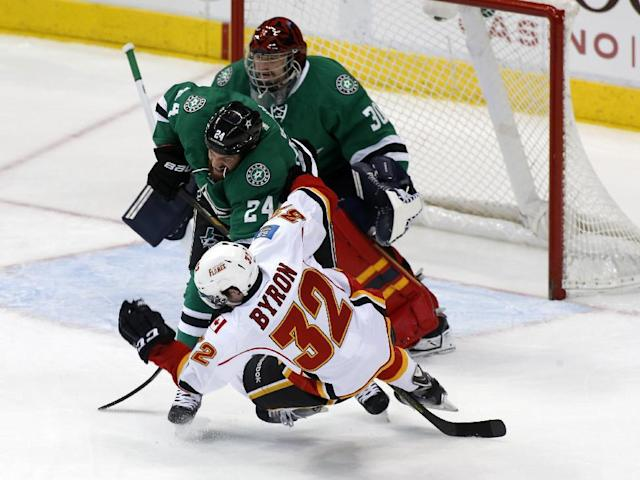 Dallas Stars goalie Tim Thomas (30) watches as defenseman Jordie Benn (24) knocks Calgary Flames center Paul Byron (32) away from the goal in the first period of an NHL hockey game on Friday, March 14, 2014, in Dallas. (AP Photo/Sharon Ellman)