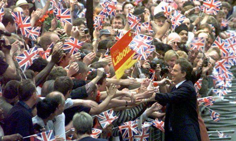 Tony Blair is greeted by a sea of flag-waving well-wishers as he arrives in Downing Street after Labour's 1997 election victory.