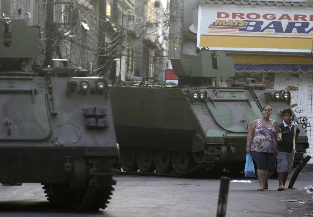 Residents walk past Brazilian Navy armored vehicles during an operation at the Mare slums complex in Rio de Janeiro March 30, 2014. The federal troops and police occupied the Mare slums complex on Sunday to help quell a surge in violent crime following attacks by drug traffickers on police posts in three slums on the north side of the city, government officials said. Less than three months before Rio welcomes tens of thousands of foreign soccer fans for the World Cup, the attacks cast new doubts on government efforts to expel gangs from slums using a strong police presence. The city will host the Olympics in 2016. REUTERS/Ricardo Moraes (BRAZIL - Tags: CRIME LAW SOCIETY)