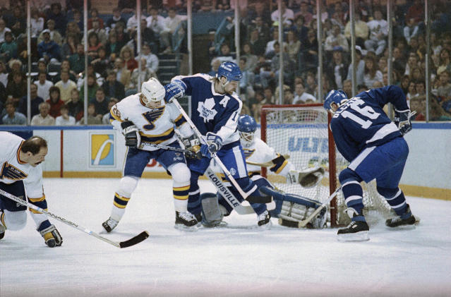 FILE - In this Friday, April 7, 1990 file photo, St. Louis Blues goalie Curtis Joseph makes a leg save against the Toronto Maple Leafs' Ed Olczyk (16) while teammate Wendel Clark (17) looks on during first period action of their NHL playoff game in St. Louis. The NHL hasn't had best-of-five playoff series since 1986. That's changing for this year with the league expanding to 24 playoff teams as part of its restart. The qualifying round will feature 16 teams facing off in best-of-five series to determine who moves on. (AP Photo/Andy Hoekstra, File)