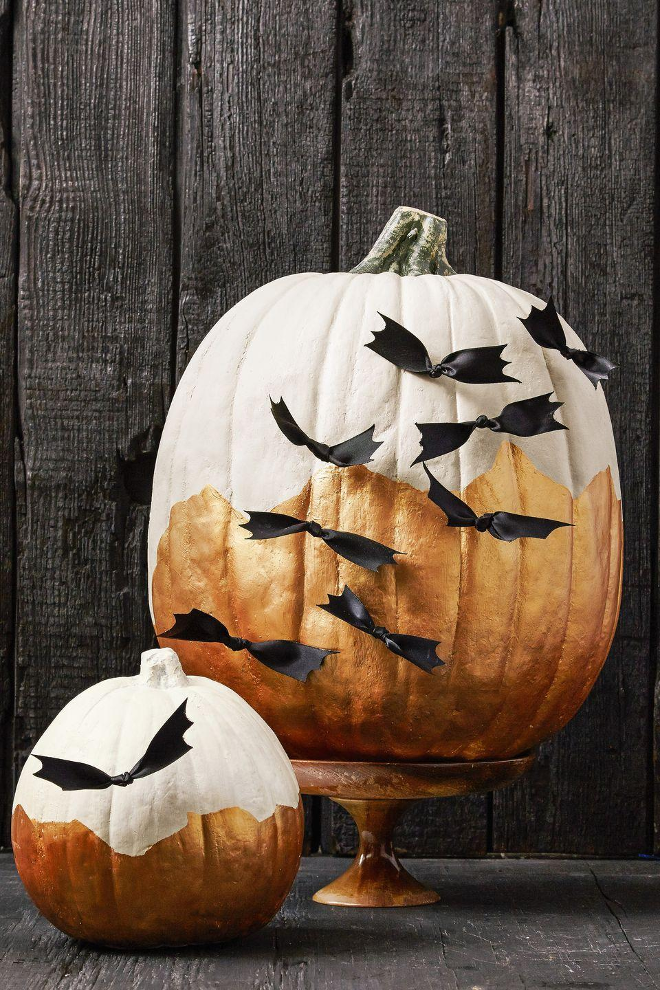"""<p>Here's a batty idea: After painting your pumpkin, tie a loose knot in the middle of a four-inch piece of black satin ribbon, then cut the ends to resemble wings. Once you have a cauldron of bats, attach them to a painted pumpkin with sewing pins. </p><p><a class=""""link rapid-noclick-resp"""" href=""""https://www.amazon.com/Black-Double-Face-Satin-Ribbon/dp/B00CIXSW0M?tag=syn-yahoo-20&ascsubtag=%5Bartid%7C10055.g.2592%5Bsrc%7Cyahoo-us"""" rel=""""nofollow noopener"""" target=""""_blank"""" data-ylk=""""slk:SHOP RIBBON"""">SHOP RIBBON</a></p>"""