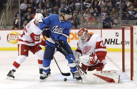 Jan 11, 2019; Winnipeg, Manitoba, CAN; Winnipeg Jets left wing Kyle Connor (81) looks for a rebound after Detroit Red Wings goaltender Jonathan Bernier (45) blocks a shot in the second period at Bell MTS Place. Mandatory Credit: James Carey Lauder-USA TODAY Sports