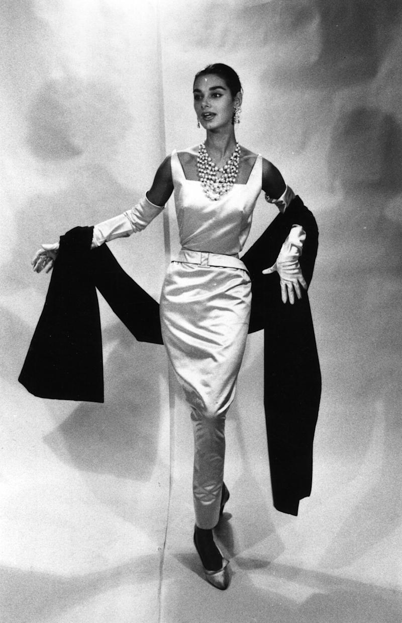 A model wears a white satin dinner dress with a stole by Givenchy.
