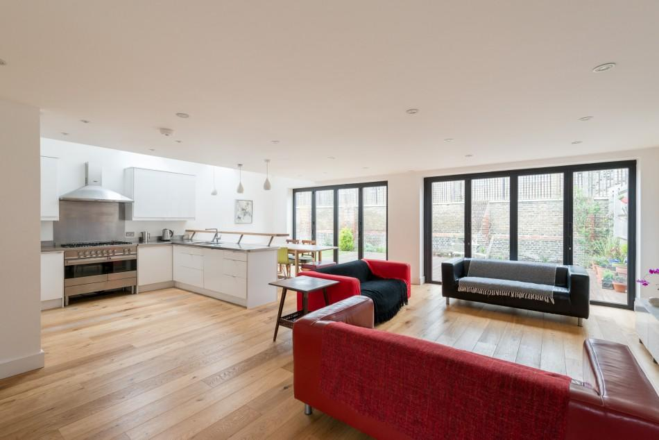 <p>One of the most outstanding features of the home is this vast, open plan living room combined with a kitchen and dining area. Huge cantilever doors flood the room with natural light and open onto the extensive decking area and garden. </p>