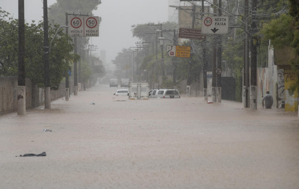 Vehicles are stuck in a flooded street in Sao Paulo, Brazil, Monday, Feb. 10, 2020. Heavy rains flooded the city, causing its main river to overflow its banks. (AP Photo/Andre Penner)