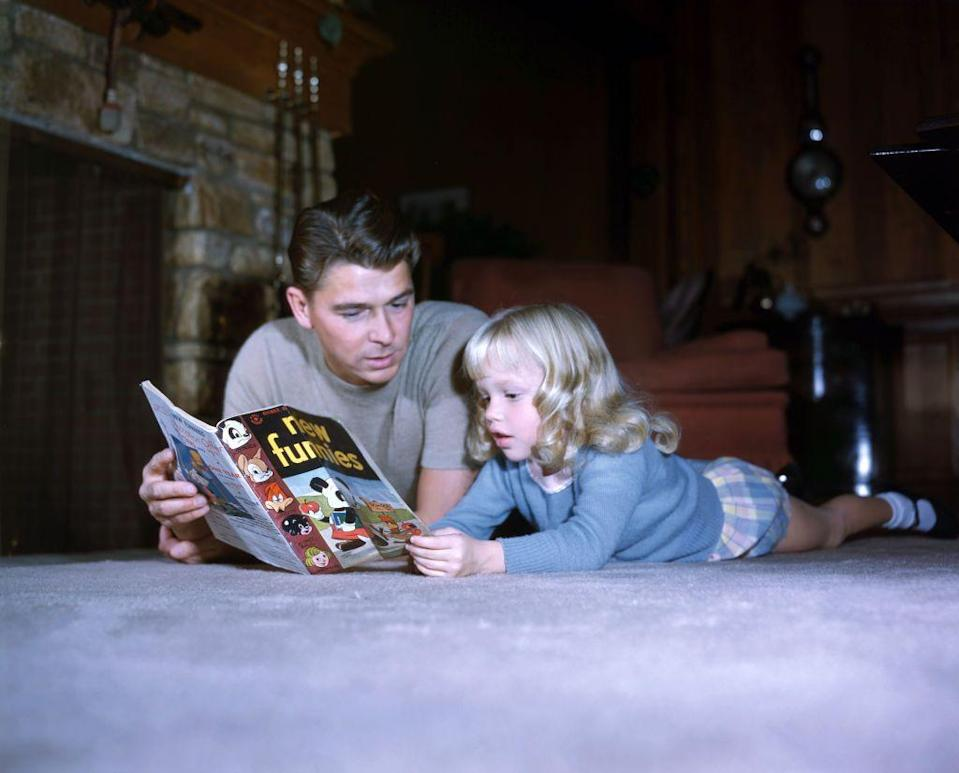 <p>Ronald Reagan lies on the living room floor of his Bel-Air home as he reads a comic book with his daughter Maureen in 1945. </p>