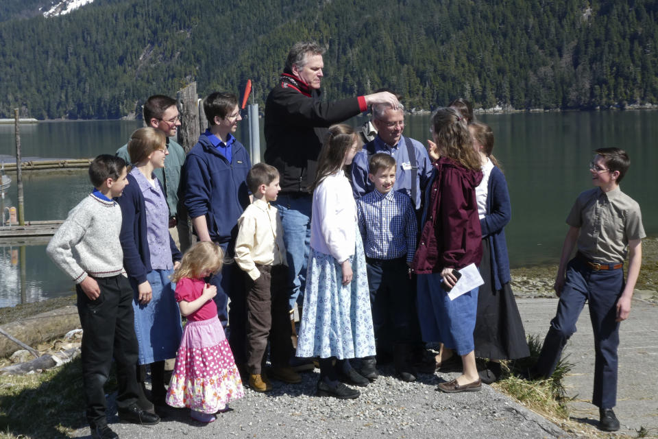 Alaska Gov. Mike Dunleavy, center, gathers with members of Mark and Amy Bach's family as they prepare to pose for a photo on Thursday, April 22, 2021, in Hyder, Alaska. The family also invited Dunleavy to their home before he left Hyder, a small community near the U.S.-Canada border and one of the stops on Dunleavy's one-day visit to southeast Alaska communities on April 22, 2021. (AP Photo/Becky Bohrer)