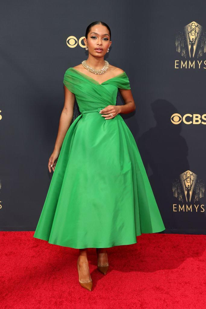 Yara Shahidi on the red carpet in a bright green calf length '50s style dress