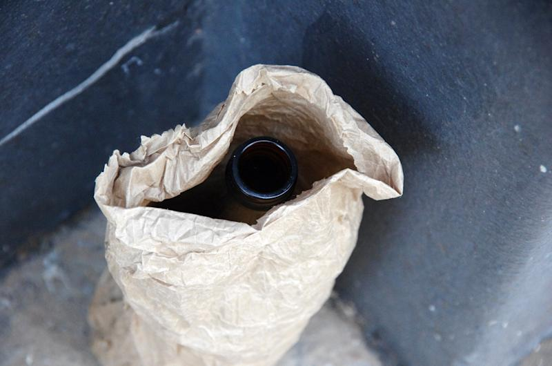 Empty alcohol bottle in a brown paper bag left in the alley next to building