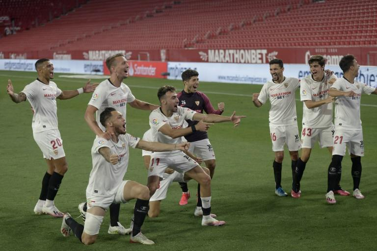 Sevilla players celebrate in front of empty stands at the Ramon Sanchez Pizjuan after their 2-0 win over Betis as La Liga returned from a three-month suspension on Thursday