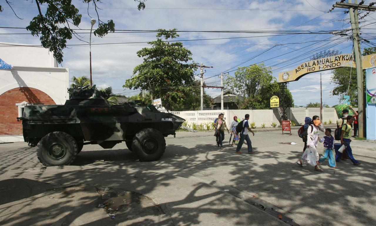 Residents walk past a government military vehicle as they evacuate near an area where members of Muslim rebels Moro National Liberation Front (MNLF) have occupied in Zamboanga city, southern Philippines September 9, 2013. Muslim rebels took 30 civilian hostages in the southern Philippines on Monday and held security forces in a standoff as part of a drive to derail peace talks, officials said. Police commandos cordoned off parts of Zamboanga city on the island of Mindanao after a rogue faction of the MNLF took hostages and tried to march to the city hall to raise their flag, an army commander said. REUTERS/Stringer (PHILIPPINES - Tags: POLITICS MILITARY CIVIL UNREST)