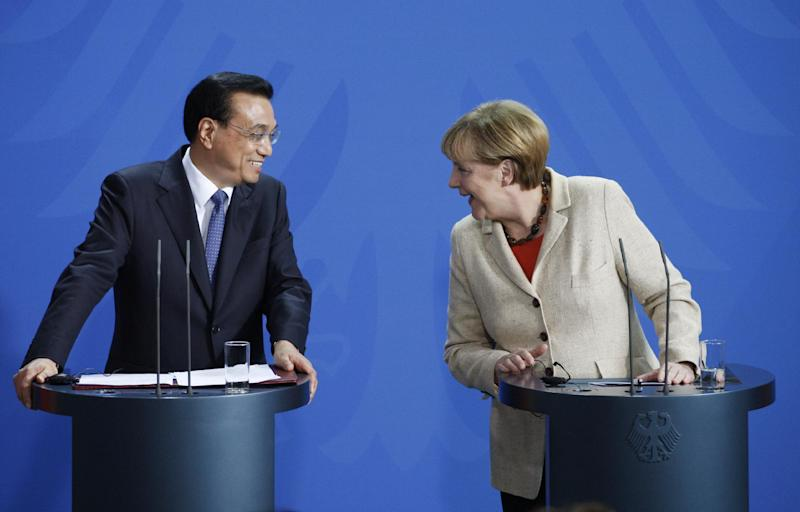 Chinese Prime Minister Li Keqiang (L) and German Chancellor Angela Merkel (R) lean towards each other as they address a press conference in Berlin on October 10, 2014 (AFP Photo/Odd Andersen)