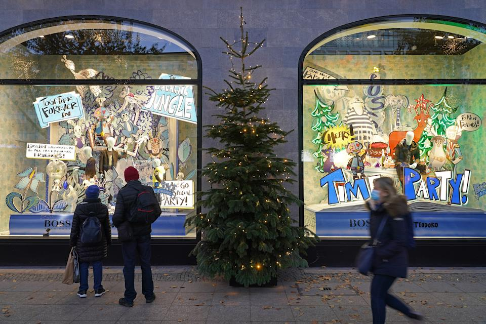 BERLIN, GERMANY - NOVEMBER 23: People wearing protective face masks walk past Christmas display windows of KaDeWe department store during the second wave of the coronavirus pandemic on November 23, 2020 in Berlin, Germany. The Christmas season is beginning muted in Berlin, with traditional Christmas markets that would normally open today all cancelled. Germany is in the midst of November semi-lockdown measures that political leaders will likely be extended until December 20 as authorities continue to struggle to bring down coronavirus infection rates.  (Photo by Sean Gallup/Getty Images)