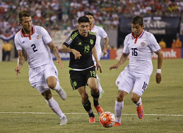 Mexico's Oribe Peralta (19) is defended by Costa Rica's Francisco Calvo (2) and Christian Gamboa (16) during the second half of a CONCACAF Gold Cup soccer match Sunday, July 19, 2015, at MetLife stadium in East Rutherford, N.J. (AP Photo/Seth Wenig)