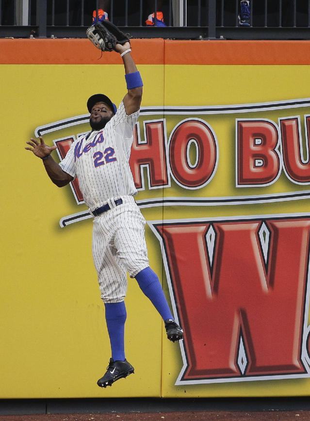 New York Mets left fielder Eric Young Jr. (22) leaps to catch a line drive hit by Atlanta Braves' Justin Upton to end the first inning of a baseball game, Tuesday, July 8, 2014, in New York. (AP Photo/Julie Jacobson)