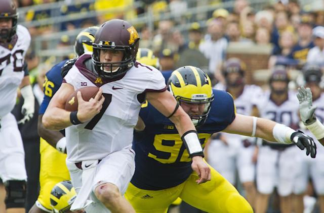 Minnesota quarterback Mitch Leidner (7) tries to break a tackle from Michigan defensive end Keith Heitzman (92) in the first quarter of an NCAA college football game, Saturday, Oct. 5, 2013, in Ann Arbor, Mich. (AP Photo/Tony Ding)