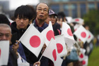 Holding nationals flags, people line up and wait outside of the Imperial Palace during the enthronement ceremony for Emperor Naruhito Tuesday, Oct. 22, 2019, in Tokyo. (AP Photo/Eugene Hoshiko)
