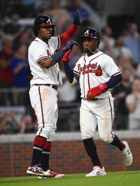 Atlanta Braves' Ronald Acuna Jr. and Ozzie Albies, right, celebrate scoring on a Freddie Freeman line drive single to left field during the seventh inning of a baseball game against the Miami Marlins, Tuesday, Aug. 20, 2019, in Atlanta. (AP Photo/John Amis)