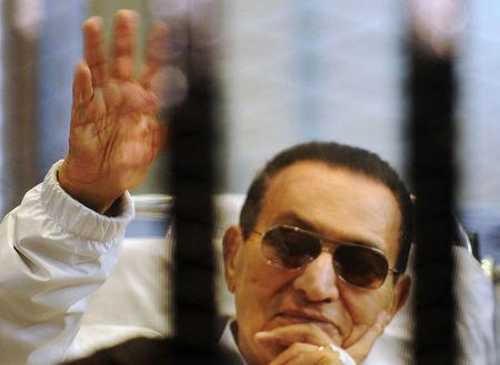 FILE PHOTO - Former Egyptian President Mubarak waves inside a cage in a courtroom at the police academy in Cairo