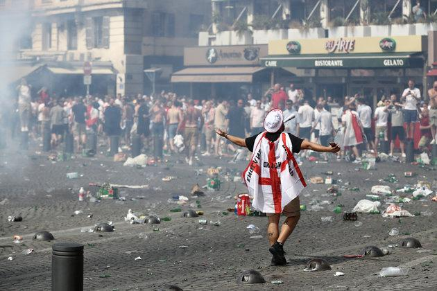 Police have confiscated the passports of hundreds of British football hooligans ahead of the World Cup; a fan wearing an England flag is pictured above during theUEFA Euro 2016 football tournament