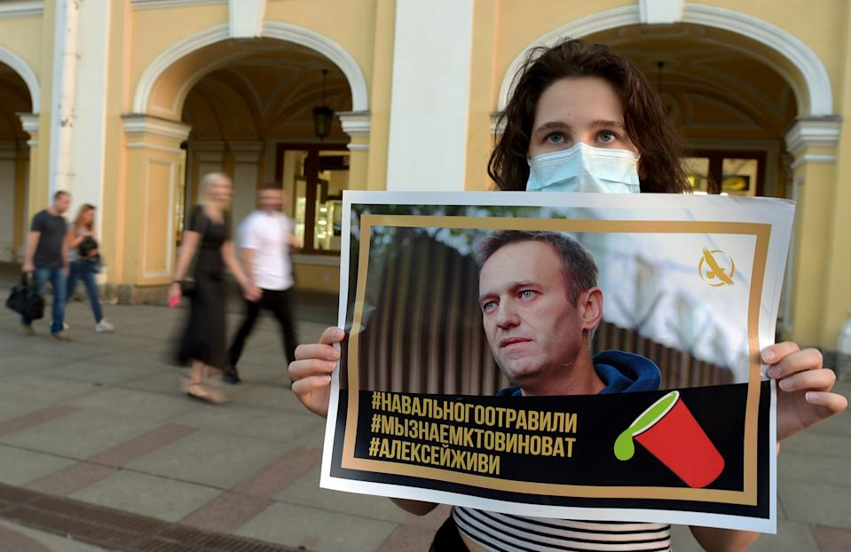 A woman holding a placard with an image of Alexei Navalny expresses support for the opposition leader after he was rushed to intensive care. Source: Getty