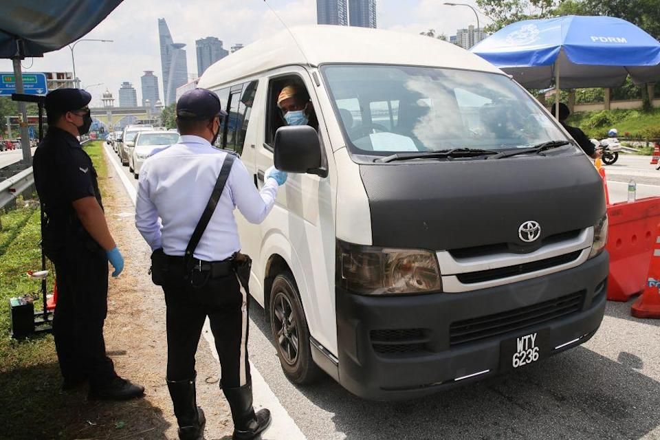 Police conduct checks on vehicles at a roadblock on the Federal Highway on the first day of Raya May 13, 2021. — Picture by Choo Choy May