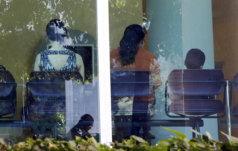 In this June 12, 2019, photo, immigrants wait inside and outside of the immigration court in Miami. The Trump administration has appointed more than 4 in 10 of the country's sitting immigration judges in a hiring surge that comes as U.S. authorities seek to crack down on immigration. (AP Photo/Brynn Anderson)