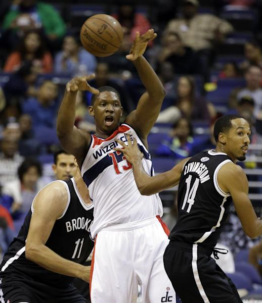 Washington Wizards forward Kevin Seraphin (13), of France, passes the ball as he is guarded by Brooklyn Nets center Brook Lopez, left, and guard Shaun Livingston (14) in the first half of an NBA preseason basketball game Tuesday, Oct. 8, 2013, in Washington. (AP Photo/Alex Brandon)