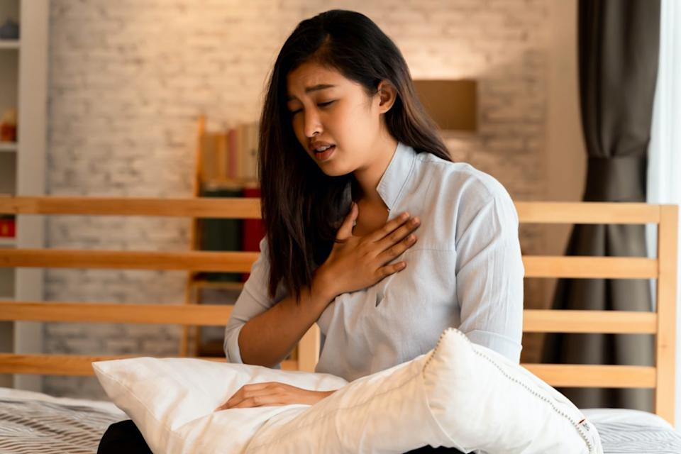 Asian woman having difficulty breathing in bedroom at night