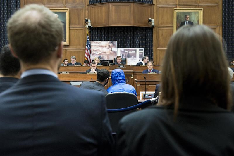 "A Syrian Army defector known as ""Caesar"" (C-blue jacket) briefs the House Foreign Affairs Committee on the torture and killing of some 10,000 anti-Assad regime activists during hearings on Capitol Hill July 31, 2014 in Washington"