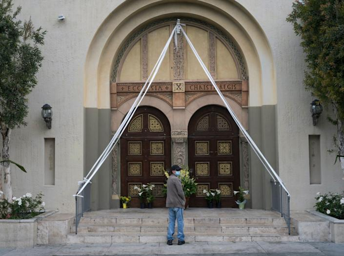 A parishioner prays outside closed doors decorated with Easter lily flowers at the Christ the King Church in Los Angeles, California, April 12, 2020.