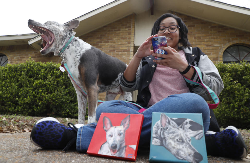 In this photo made Monday, March 2, 2020, Danielle Moore looks at her phone as she poses for photos with Kana and paintings of the pet Australian cattle dog in Dallas. In the dog-eat-dog world of online shopping, Chewy has an unusual plan to fend off Amazon: turning pets into works of art. The online pet shop surprises customers with oil paintings of their furry friends, a move the company says wins them customers for life. (AP Photo/LM Otero)