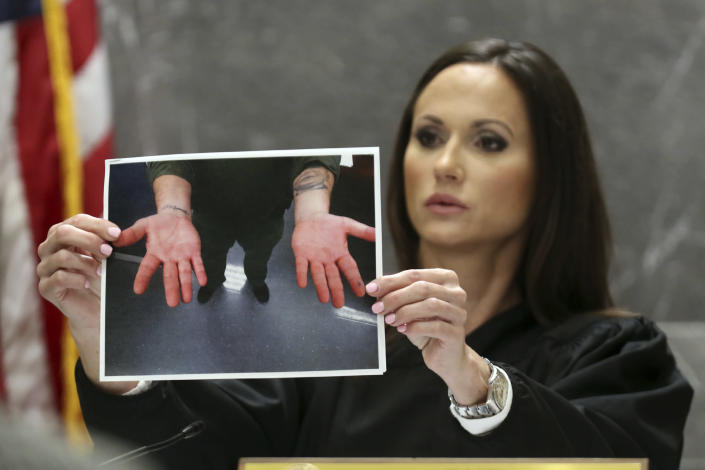 Judge Elizabeth Scherer holds a photograph of the hands of Broward jail guard Sgt. Ray Beltran after a November 2018 altercation between Beltran and Parkland school shooter Nikolas Cruz during Cruz's pre-trial hearing at the Broward County Courthouse in Fort Lauderdale, Fla., Wednesday, July 14, 2021, on four criminal counts stemming from his alleged attack on a Broward jail guard in November 2018. Cruz is accused of punching Sgt. Ray Beltran, wrestling him to the ground and taking his stun gun. (Amy Beth Bennett/South Florida Sun-Sentinel via AP, Pool)