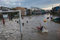 A boy bicycle-kicks a ball in a flooded area of the Belen community in Iquitos, Peru, Saturday, March 20, 2021. Despite a scandal that shook the government in Peru's capital when over 480 government officials took advantage of their privileged positions to secretly receive early inoculations ahead of healthcare workers battling the new coronavirus pandemic, 66 people with connections in Iquitos jumped the queue this week to be vaccinated against COVID-19. (AP Photo/Rodrigo Abd)