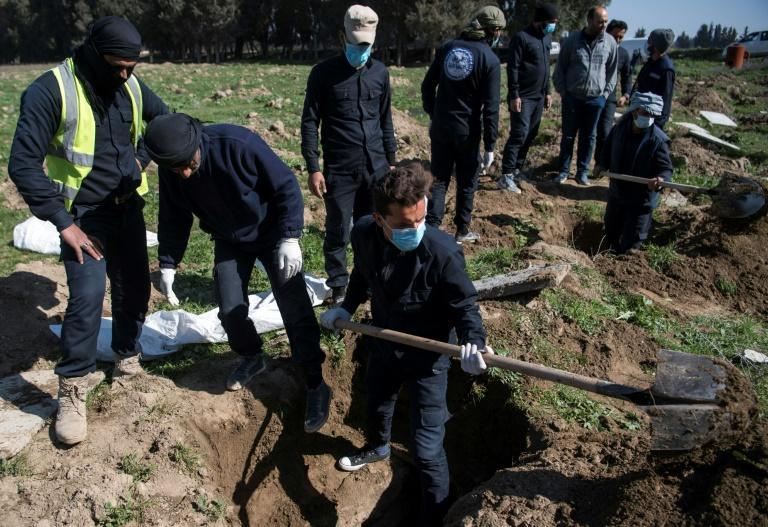 Civil defence workers excavate the site of a mass grave near the northern Syrian city of Raqa which may also contain the bodies of some foreigners imprisoned by Islamic State jihadists, whose fates remain unknown