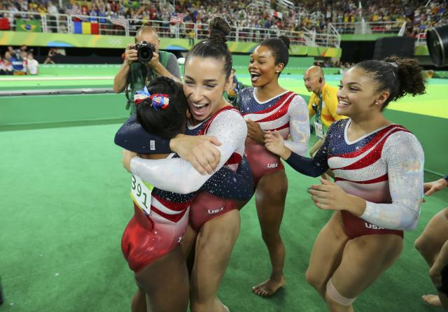 2016 Rio Olympics - Artistic Gymnastics - Final - Women's Team Final - Rio Olympic Arena - Rio de Janeiro, Brazil - 09/08/2016. Simone Biles (USA) of USA (L) is hugged by team mates Alexandra Raisman (USA) of USA (Aly Raisman), Gabrielle Douglas (USA) of USA (Gabby Douglas) and Laurie Hernandez (USA) of USA following her floor routine during the women's team final. Team USA won gold in the event. REUTERS/Mike Blake FOR EDITORIAL USE ONLY. NOT FOR SALE FOR MARKETING OR ADVERTISING CAMPAIGNS.
