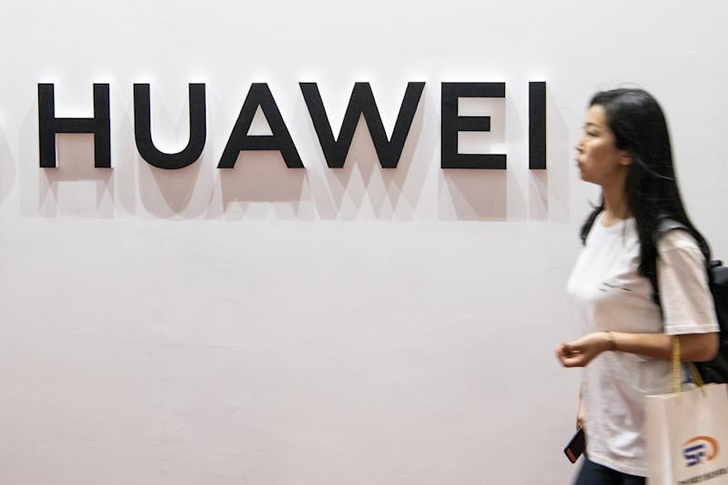 A woman walks past the Huawei logo during the Consumer Electronics Expo in Beijing on August 2, 2019. (Photo by FRED DUFOUR / AFP) (Photo credit should read FRED DUFOUR/AFP/Getty Images)