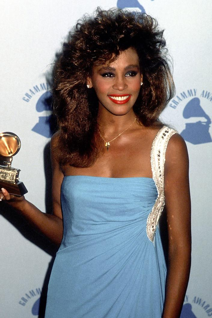 """<h3>Whitney Houston, 1986</h3><br>For her first Grammys win, Whitney Houston wore her hair soft, long, and <em>super</em> voluminous.<span class=""""copyright"""">Photo: Ron Galella Ltd./Ron Galella Collection/Getty Images.</span>"""