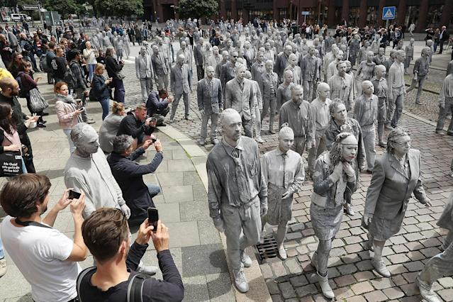 <p>Performance artists covered in clay to look like zombies walk trance-like through the city center on July 5, 2017 in Hamburg, Germany. (Friedemann Vogel/Getty Images) </p>