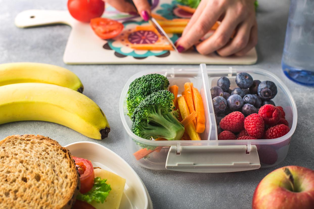Parent chopping while packing healthy lunch for school.
