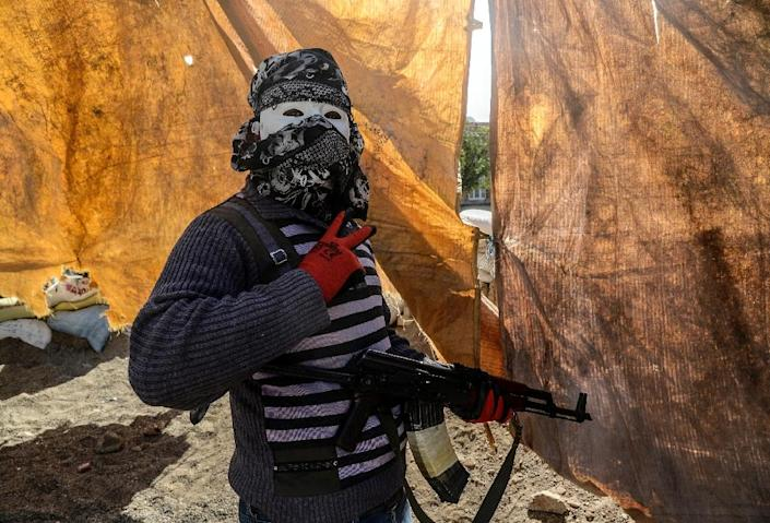 """An armed Kurdish militant of the Kurdistan Workers' Party (PKK) wearing a mask and a scarf covering his head flashes the """"V for Victory"""" sign during clashes with Turkish forces on September 28, 2015, at Bismil, in Diyarbakir (AFP Photo/Ilyas Akengin)"""