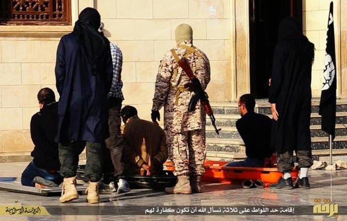 In this photo released on May 4, 2015, by a militant website, which has been verified and is consistent with other AP reporting, Islamic State militants, foreground, stand behind three men they accused of being homosexuals, as they prepare to kill them, in Raqqa city, Syria. The Washington-based Syria Justice and Accountability Center, a U.S.-based Syrian rights group, said Thursday, Jan. 16, 2020, that evidence, documents produced by the Islamic State militants themselves, could help identify individuals responsible for atrocities during the militants four-year reign of terror in Syria, thus enabling prosecution for international crimes. (Militant website via AP)